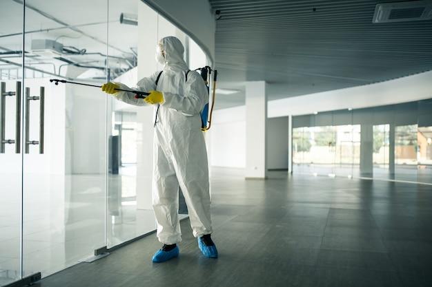 Un uomo che indossa una tuta disinfettante che spruzza con disinfettante le maniglie delle porte di vetro in un centro commerciale vuoto per prevenire la diffusione del covid-19. consapevolezza della salute, pulizia, concetto di difesa.