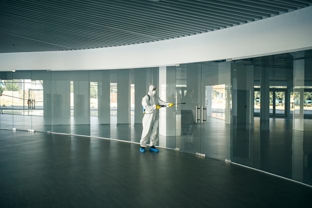 Un uomo che indossa una tuta disinfettante che spruzza con disinfettante le maniglie delle porte di vetro in un centro commerciale vuoto per prevenire la diffusione del covid-19. consapevolezza della salute, pulito, concetto di difesa.