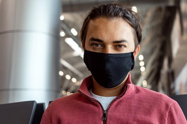Uomo che indossa la maschera per il viso in aeroporto. i temi viaggiano nella nuova normalità, coronavirus e protezione personale.