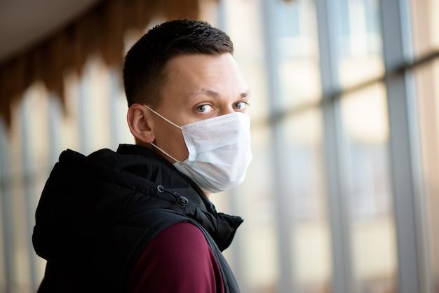 Uomo che indossa una maschera per il viso in aeroporto