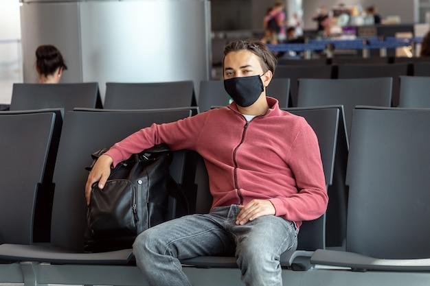 Uomo che indossa la maschera per il viso in aeroporto