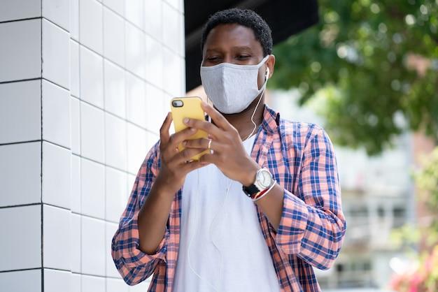 Uomo che indossa una maschera per il viso e utilizza il suo telefono cellulare in piedi all'aperto.