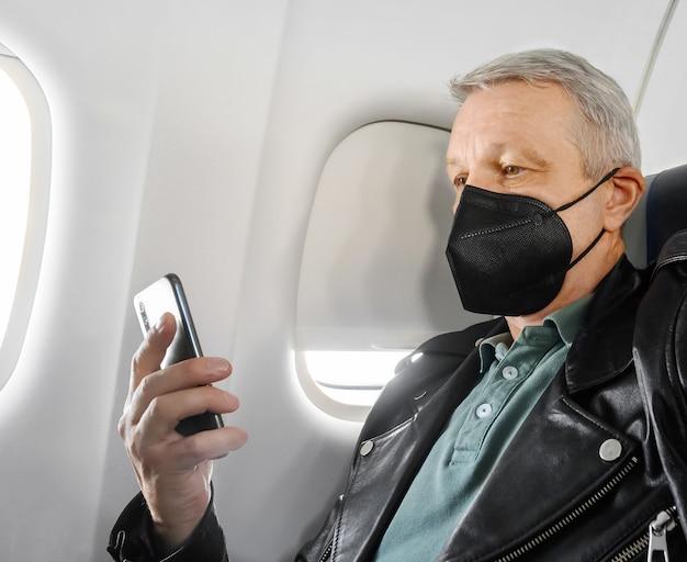 Uomo che indossa una maschera facciale e usa il telefono nella cabina dell'aereo durante il volo