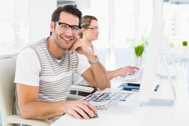 Equipaggi gli occhiali d'uso che si siedono allo scrittorio che esamina la macchina fotografica