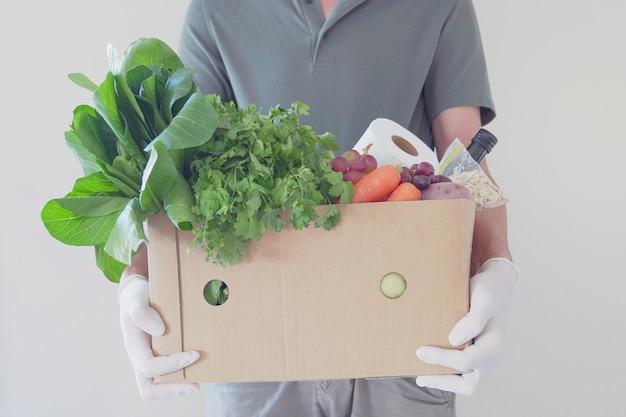 Uomo che indossa guanti che consegna scatola di cibo, volontario che tiene scatola di generi alimentari per la donazione