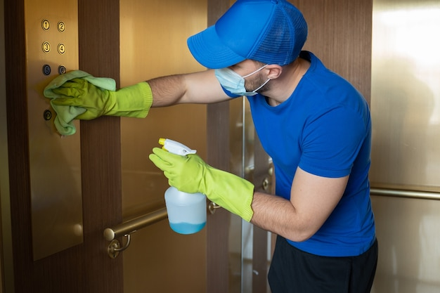 Uomo che indossa guanti e una maschera pulisce i pulsanti e il corrimano del personale addetto alle pulizie dell'ascensore disinfettando l'ascensore per evitare il contagio