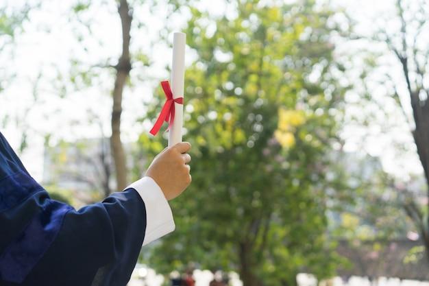 Uomo che indossa abito di laurea e in possesso di carta con certificato con nastro dopo la laurea in università