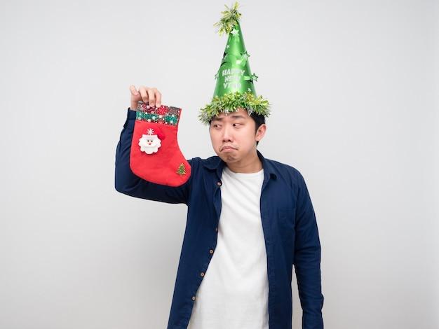 Uomo che indossa un cappello verde guardando la calza di natale in mano