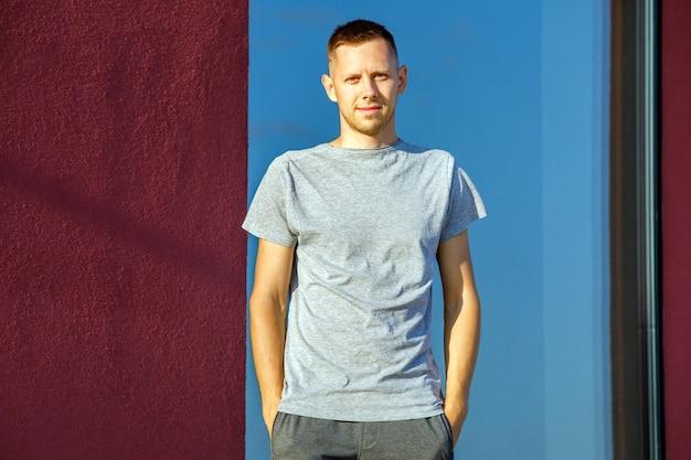 Uomo che indossa una t-shirt grigia vuota con spazio per il tuo logo, mock up o design nell'area urbana