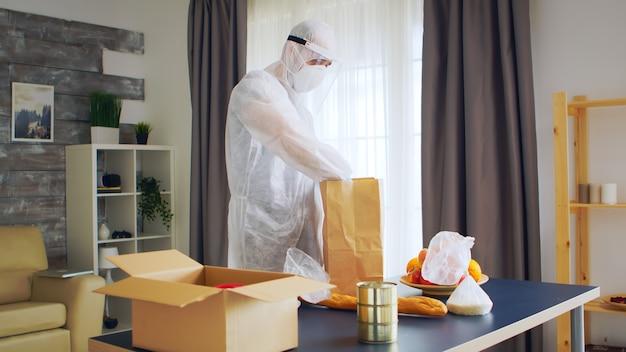 Uomo che indossa una tuta ignifuga che mette una bottiglia di olio nel pacchetto per il cliente online durante il covid-19.