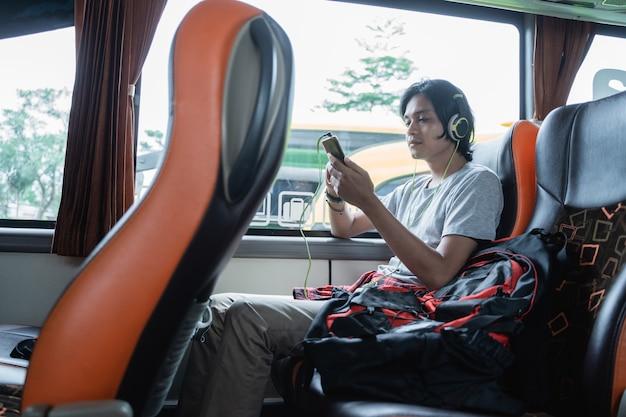 Un uomo che indossa le cuffie mentre ascolta la musica da un handphone mentre è seduto vicino alla finestra durante un viaggio in autobus