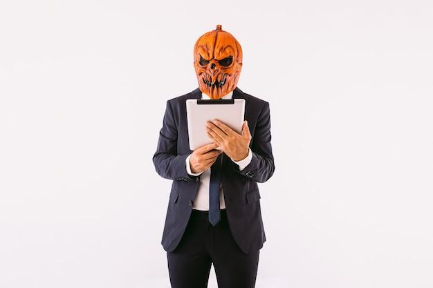 Uomo che indossa giacca, cravatta blu e maschera zucca jack-o-lantern che consulta un tablet, su sfondo bianco. concetto di celebrazione di halloween e carnevale.