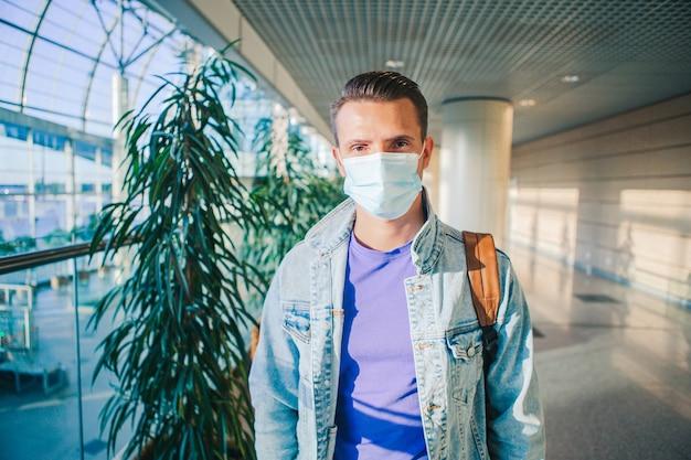 Uomo che indossa una maschera per prevenire il virus nella lounge dell'aeroporto internazionale in attesa del volo aereo.