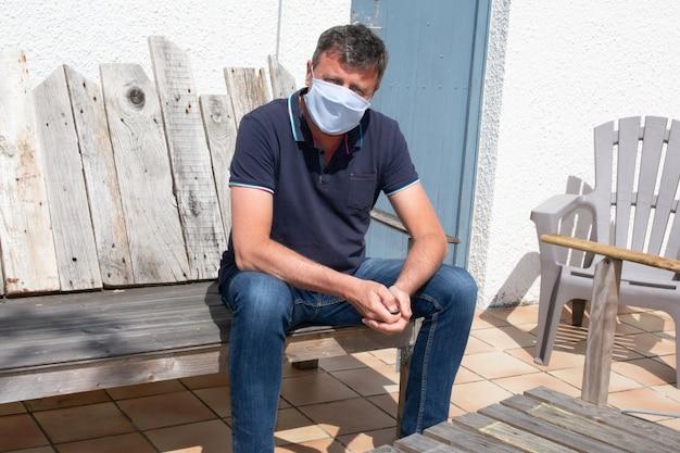 Equipaggi indossare la maschera medica all'aperto nel giardino domestico residenziale nella quarantena di coronavirus in casa