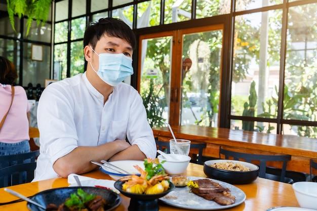 Uomo che indossa una maschera medica per proteggere il coronavirus nel ristorante