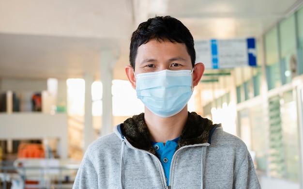 L'uomo che indossa una maschera medicinale nell'area pubblica aziendale si protegge dal rischio di malattie, le persone prevengono l'infezione da coronavirus covid-19 o dall'inquinamento atmosferico.