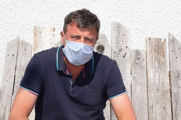 L'uomo che indossa una maschera protettiva all'aperto per prevenire i germi covid-19 del coronavirus si siede sulla panca di legno fatta in casa