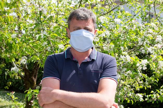 Uomo che indossa una maschera medica protettiva per la protezione dalla malattia da virus nel giardino di casa in sicurezza sanitaria e coronavirus concetto pandemico