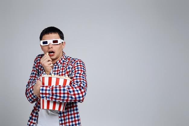 Uomo con gli occhiali 3d rosso-blu e mangiando popcorn dal secchio mentre si guarda un film horror isolato su grigio