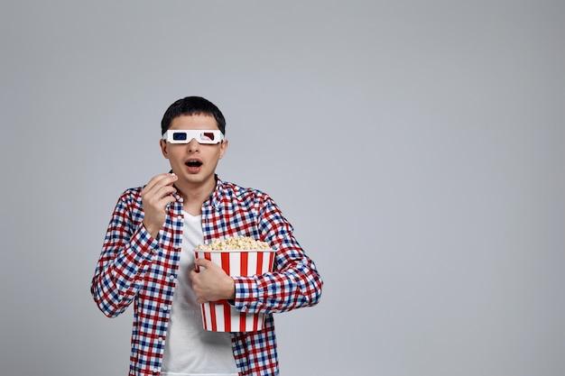 Uomo che indossa occhiali 3d rosso-blu e mangia popcorn dal secchio mentre si guarda un film isolato su grigio
