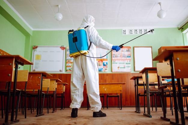 Un uomo che indossa un'attrezzatura igienizzante e una tuta protettiva disinfetta l'aula per prevenire la diffusione del coronavirus tra studenti e alunni. assistenza sanitaria e concetto di prevenzione covid-19.