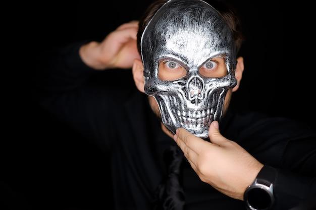 Un uomo che indossa una maschera da scheletro, la corregge con le mani