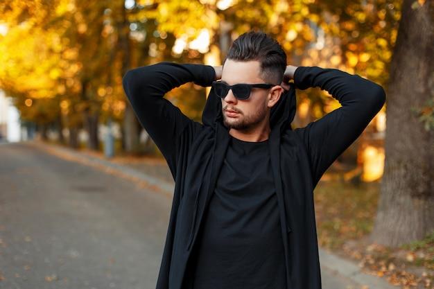 Uomo che indossa occhiali da sole in una felpa con cappuccio nera veste un cappuccio sulla strada, la giornata di sole autunnale