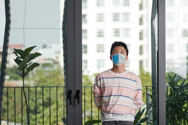 Uomo che indossa una maschera chirurgica che guarda fuori dalla finestra di casa. coronavirus, covid-19 e concetto di quarantena.