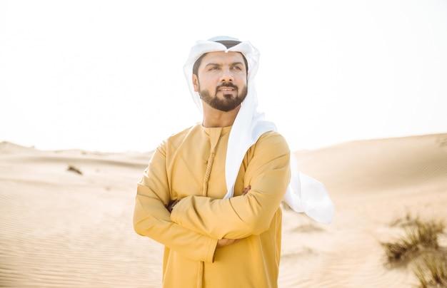 Uomo che indossa abiti tradizionali degli emirati arabi uniti trascorrere del tempo nel deserto