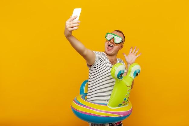 Uomo che indossa la maschera subacquea, maglietta a righe, nuotate guardando nel telefono, prendendo un selfie