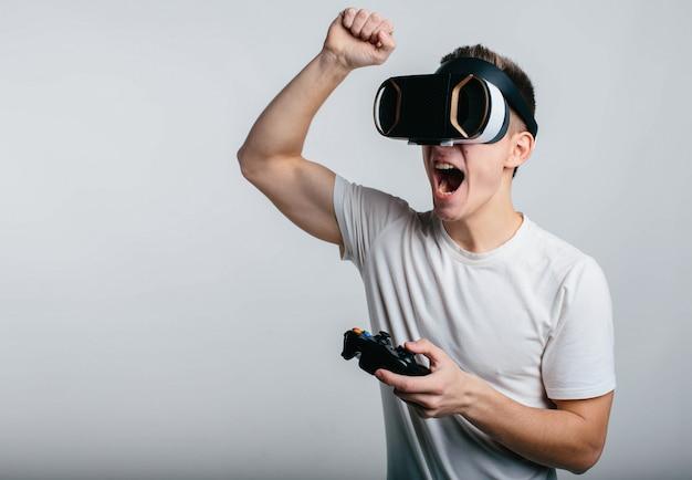 Equipaggi gli occhiali di protezione d'uso di realtà virtuale e la tenuta del gamepad mentre stanno vicino alla lavagna bianca
