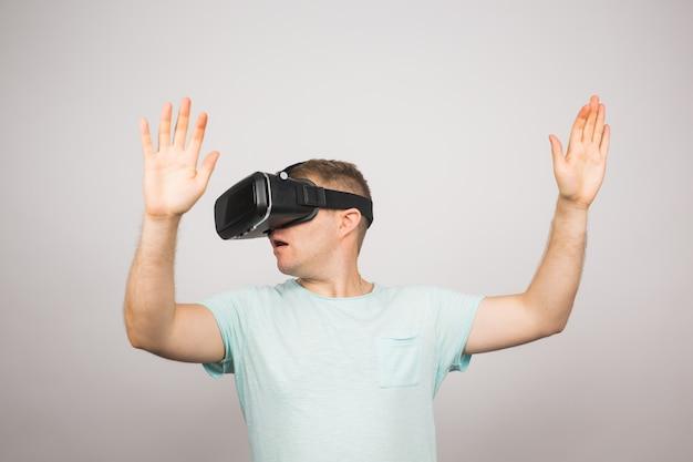 Uomo che indossa occhiali per realtà virtuale. studio girato, grigio