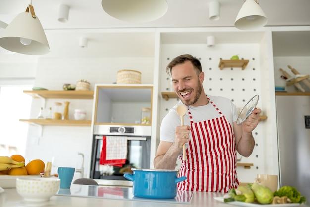 Uomo che indossa un grembiule bianco con linee rosse e cucina qualcosa in cucina