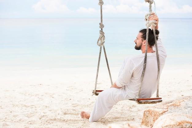 Uomo bianco che indossa seduto sull'altalena della spiaggia e sognare