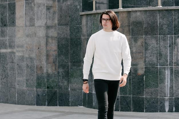 Uomo che indossa felpa bianca o felpa con cappuccio e occhiali fuori per le strade della città.