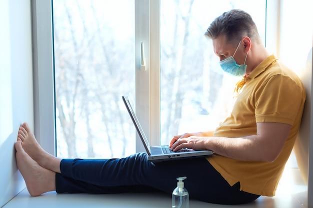 Un uomo indossa una maschera medica per prevenire il coronavirus mentre lavora vicino a una finestra