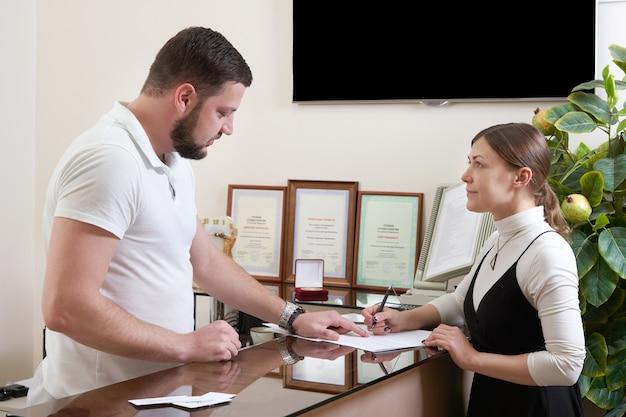 Uomo che accoglie cliente giovane donna alla reception dell'ufficio