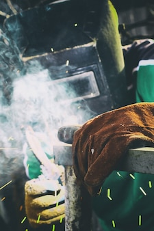 Un uomo in maschera di saldatura con saldatura elettrica in mano che salda un telaio metallico.