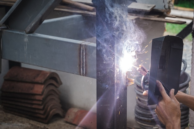 Saldatore dell'uomo che fa una struttura di scala metallica in un edificio residenziale utilizzando una saldatrice.