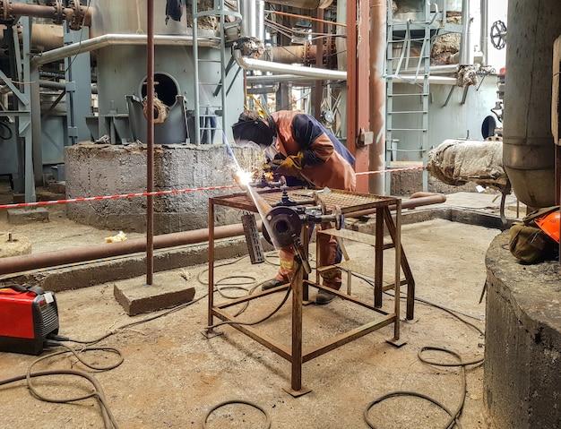 Un saldatore dell'uomo è impegnato nella saldatura del metallo sulla conduttura e sulle flange