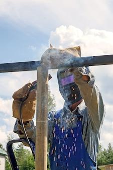Saldatore uomo con maschera di saldatura, uniforme da costruzione e guanti protettivi cucina il metallo in un cantiere stradale. costruzione di un padiglione, pergolato vicino a una casa di campagna in una giornata estiva.