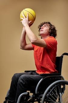 L'uomo sulla sedia a rotelle sta giocando una palla per rafforzare i muscoli, tenendo la palla da basket gialla. stile di vita delle persone con disabilità, sfondo beige isolato