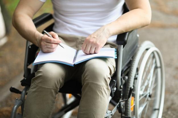L'uomo in sedia a rotelle si siede e tiene il taccuino e la penna.