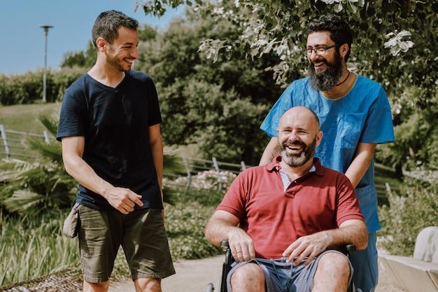 Un uomo su sedia a rotelle con il suo assistente e un amico