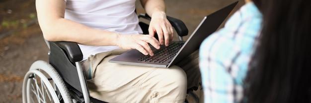 L'uomo in sedia a rotelle lavora al laptop in strada accanto alla donna si siede e tiene il tablet