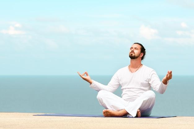 Uomo in abiti bianchi che medita yoga in riva al mare