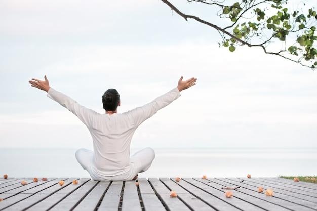 Uomo in abiti bianchi che medita yoga sul molo di legno
