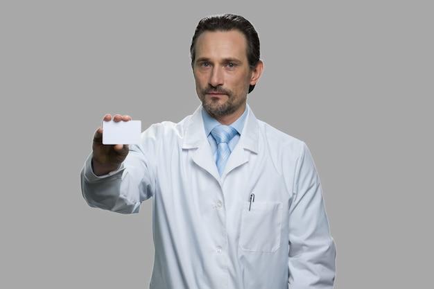 L'uomo in camice bianco tiene il biglietto da visita. medico maschio o sviluppatore scientifico con carta in mano in piedi su sfondo grigio.