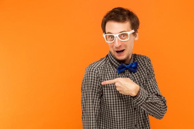 Uomo con gli occhiali bianchi che guarda la telecamera e punta il dito sullo spazio della copia