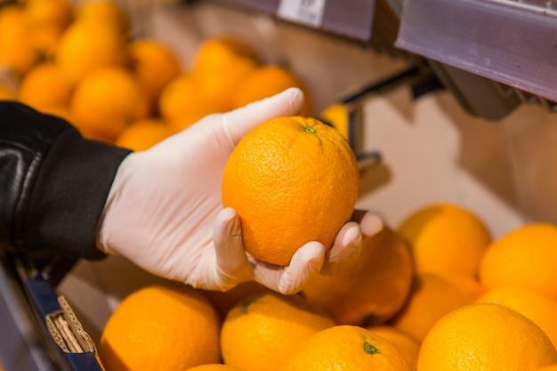 Un uomo in guanti bianchi in un negozio compra cibo. l'uomo tiene un'arancia in mano